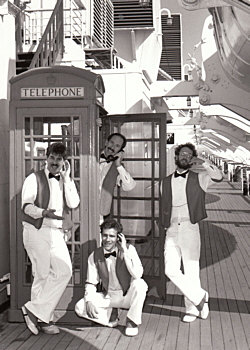 "This is an old publicity B&W photo of our barbershop quartet, taken in 1987. There's the baby-faced me at the far left, along with fellow barbershoppers (from L to R) Ken Neufeld (peeking out of the phone booth), Bill New, and Kevin Dalbey, on board the deck of the Queen Mary down in Long Beach Harbor. During our barbershop singing gigs there, we would stroll along the deck, serenading unsuspecting passers-by. Kind of ""drive-by barbershopping"", if you will..."